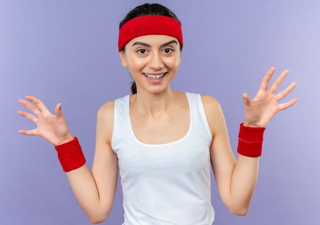 Mujer joven fitness en ropa deportiva con diadema levantando palmas en rendición sonriendo de pie sobre la pared púrpura