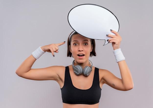 Mujer joven fitness en ropa deportiva con diadema con signo de burbuja de discurso en blanco apuntando con el dedo hacia él mirando sorprendido de pie sobre la pared blanca