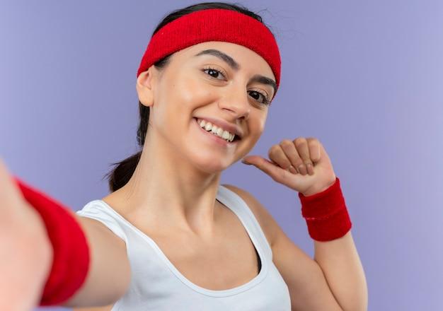 Mujer joven fitness en ropa deportiva con diadema sonriendo alegremente haciendo gesto de bienvenida con las manos de pie sobre la pared púrpura