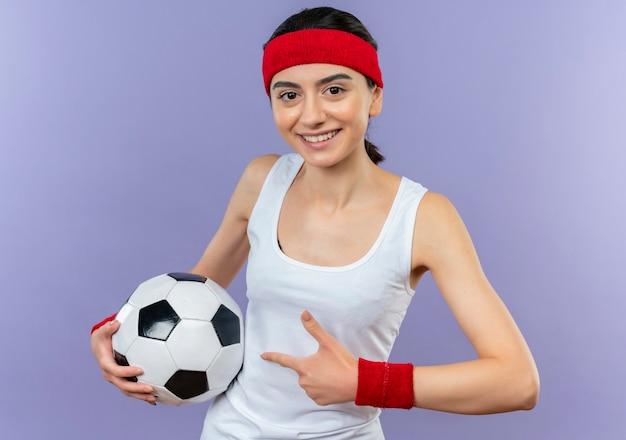 Mujer joven fitness en ropa deportiva con diadema sosteniendo un balón de fútbol apuntando con el dedo índice a él sonriendo de pie sobre la pared púrpura