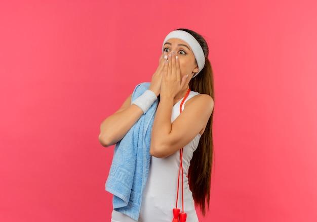 Mujer joven fitness en ropa deportiva con diadema y toalla en su hombro sorprendido cubriendo la boca con las manos de pie sobre la pared rosa