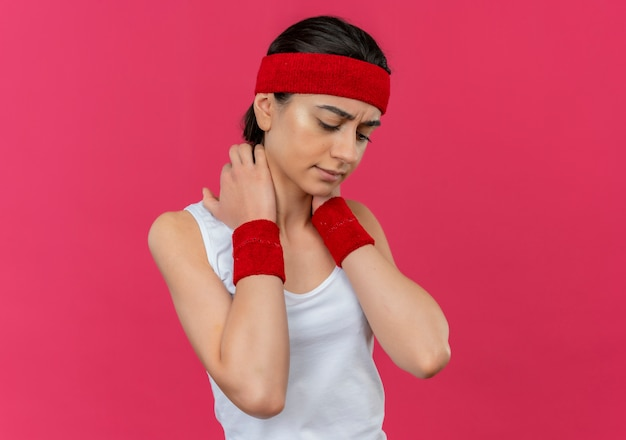 Mujer joven fitness en ropa deportiva con diadema tocando su cuello mirando malestar malestar de pie sobre la pared rosa