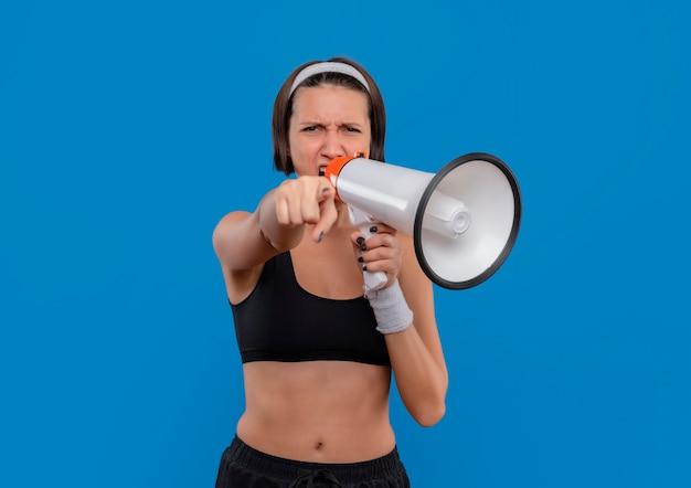 Mujer joven fitness en ropa deportiva gritando al megáfono con expresión agresiva apuntando con el dedo índice a la cámara de pie sobre la pared azul