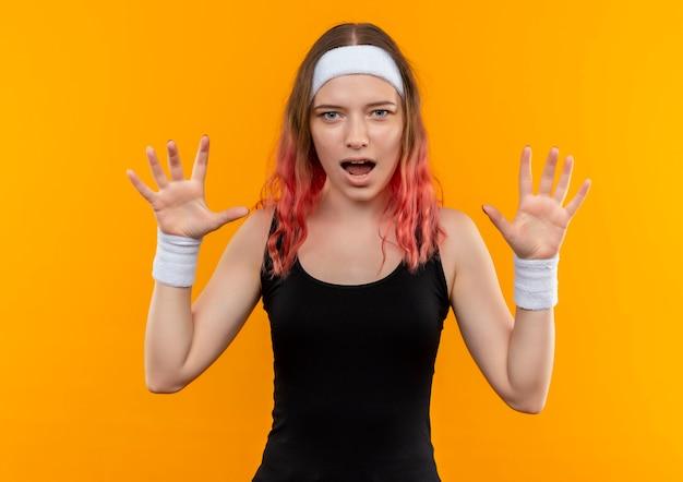 Mujer joven fitness en ropa deportiva mirando sorprendido levantando las manos en rendición de pie sobre la pared naranja
