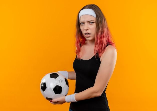 Mujer joven fitness en ropa deportiva sosteniendo un balón de fútbol descontento y confundido de pie sobre la pared naranja