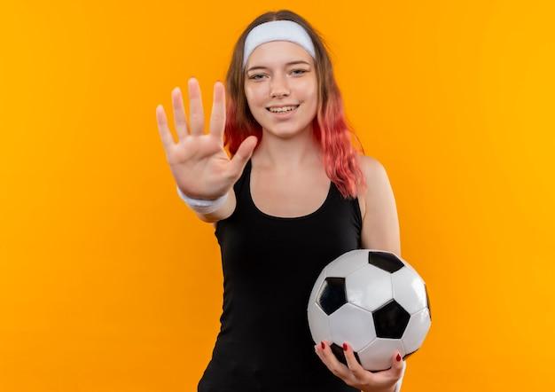 Mujer joven fitness en ropa deportiva sosteniendo un balón de fútbol haciendo señal de stop con la mano, sonriendo de pie sobre la pared naranja