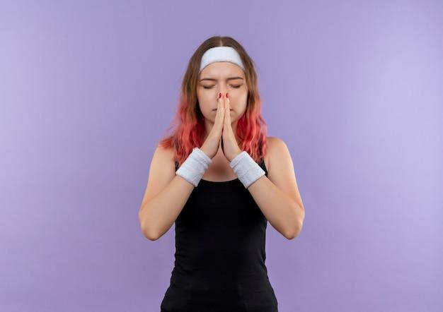 Mujer joven fitness en ropa deportiva sosteniendo las palmas juntas como rezar con los ojos cerrados con expresión de esperanza de pie sobre la pared púrpura