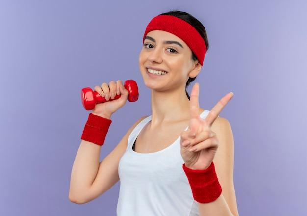 Mujer joven fitness en ropa deportiva sosteniendo pesas, posando y mostrando el signo de la victoria sonriendo alegremente de pie sobre la pared púrpura