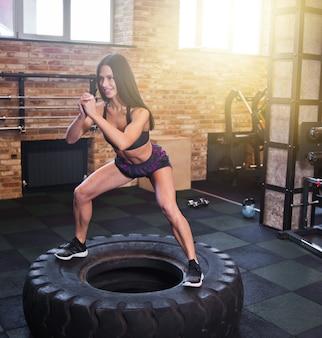 Mujer joven fitness saltando sobre una gran rueda en el gimnasio. entrenamiento funcional