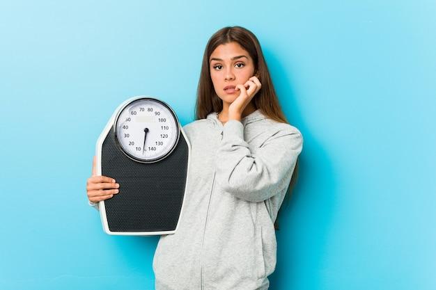Mujer joven fitness sosteniendo una escala mordiéndose las uñas, nerviosa y muy ansiosa.