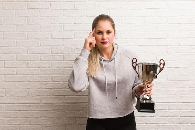 Mujer joven fitness sosteniendo un trofeo
