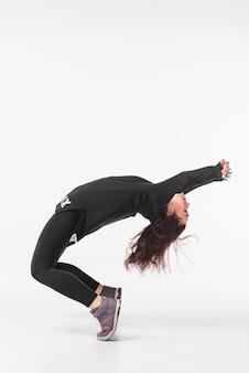 Mujer joven flexible bailando contra el telón de fondo blanco