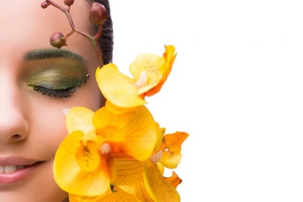 Mujer joven con la flor de la orquídea aislada en blanco