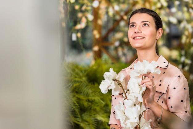 Mujer joven con flores blancas en las manos
