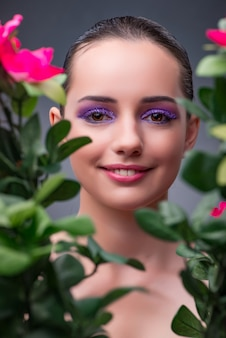 Mujer joven con flores en concepto de belleza