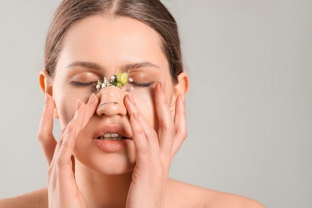 Mujer joven con flores en el rostro contra un fondo gris. concepto de cirugía plástica
