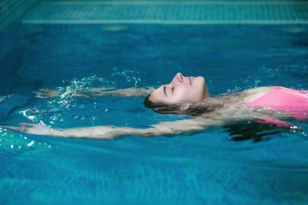 Mujer joven flotando y descansando en la piscina