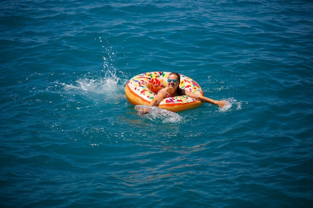 Mujer joven flotando en una dona grande inflable en el mar turquesa transparente. vista de una esbelta dama relajante de vacaciones en turquía, egipto, mar mediterráneo.