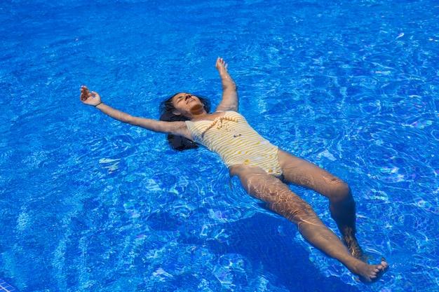 Mujer joven flotando en la piscina