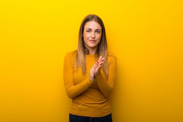 Mujer joven en fondo amarillo que aplaude después de la presentación en una conferencia