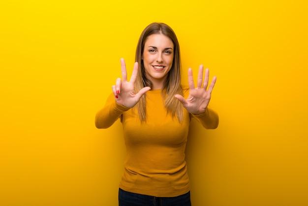 Mujer joven en el fondo amarillo que cuenta ocho con los dedos
