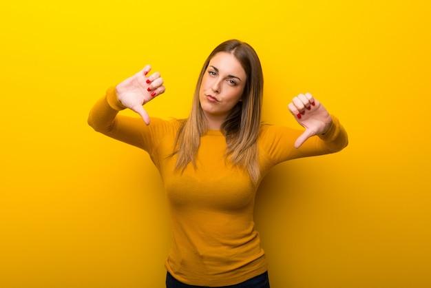 Mujer joven en el fondo amarillo que muestra el pulgar hacia abajo con ambas manos