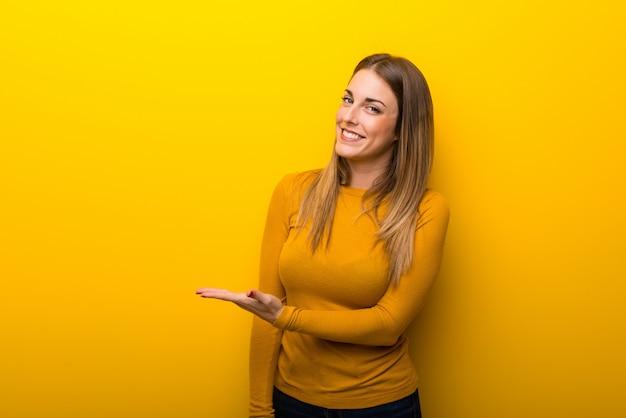 Mujer joven en el fondo amarillo que presenta una idea mientras que mira sonriente hacia