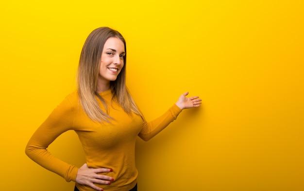 Mujer joven en fondo amarillo que señala detrás y que presenta un producto