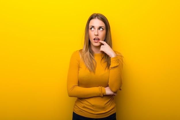 Mujer joven en el fondo amarillo que tiene dudas mientras que mira para arriba