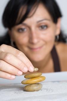 Mujer joven de fondo la construcción de piedras de equilibrio