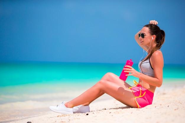 Mujer joven en forma activa en su ropa deportiva durante vacaciones en la playa
