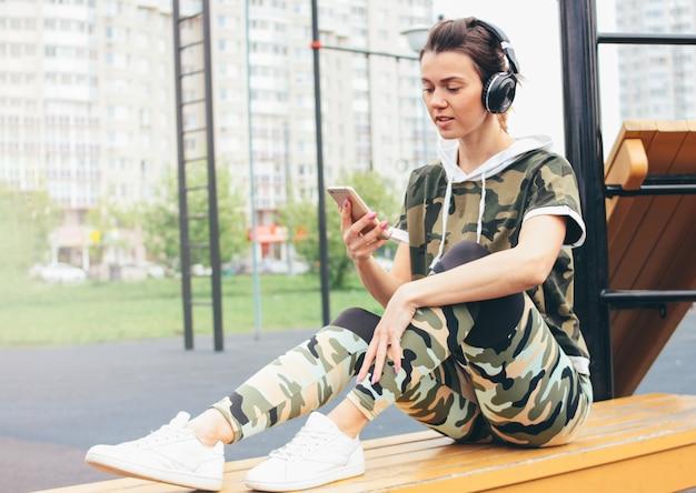 Mujer joven en forma atractiva en auriculares y ropa deportiva de color militar haciendo entrenamiento con móvil