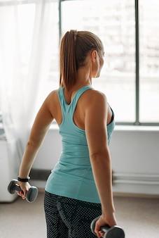 Mujer joven en forma atractiva en ropa deportiva modelo de fitness niña entrena con pesas en las clases de entrenamiento de estudio en casa