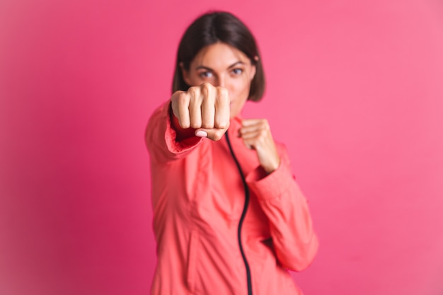 Mujer joven en forma en chaqueta de deporte en rosa lucha contra el gesto de la caja