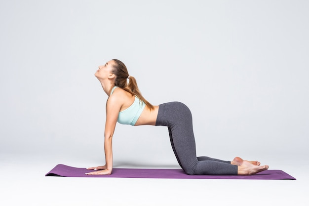 Mujer joven en forma en clase de yoga. atractiva mujer morena con cola de caballo practicando yoga. concepto de deporte y estilo de vida saludable. serie de poses de ejercicio aisladas.