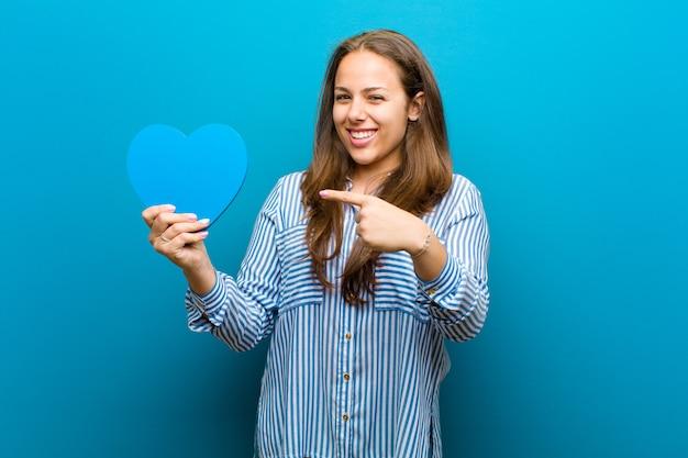 Mujer joven con forma de corazón contra azul