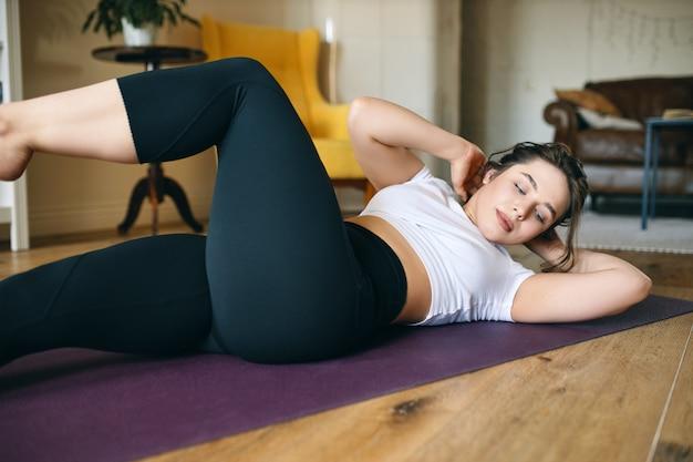 Mujer joven en forma deportiva en ropa deportiva acostada boca arriba sobre una colchoneta de fitness haciendo abdominales cruzados o abdominales diagonales para desarrollar los músculos abdominales.