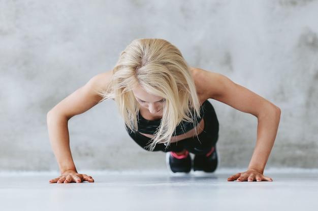 Mujer joven en forma en la formación de ropa deportiva
