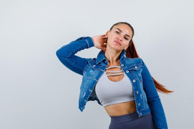 Mujer joven en forma manteniendo la mano detrás del cuello en la parte superior, chaqueta de mezclilla y aspecto triste. vista frontal.