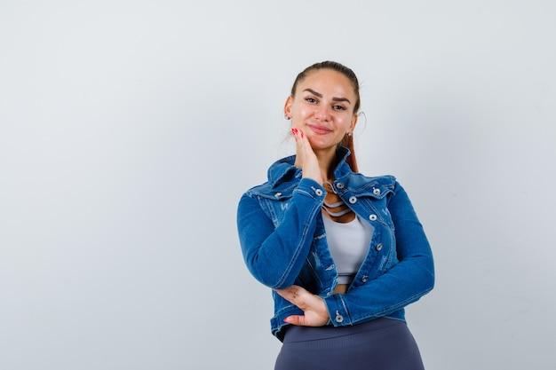 Mujer joven en forma en la parte superior, chaqueta de mezclilla manteniendo la mano en la mejilla y luciendo feliz, vista frontal.