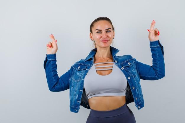 Mujer joven en forma en la parte superior, chaqueta de mezclilla que muestra los dedos cruzados y se ve alegre, vista frontal.
