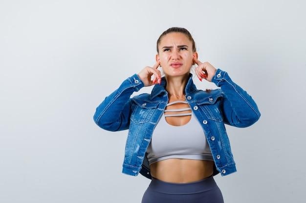 Mujer joven en forma en la parte superior, chaqueta de mezclilla tapando las orejas con los dedos y mirando molesto, vista frontal.