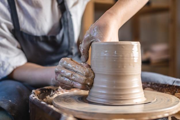 Mujer joven formando la arcilla con sus manos creando jarra en un taller.