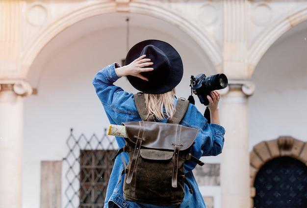 Mujer joven, fotógrafa profesional con cámara en antiguo castillo.