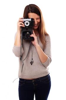 Mujer joven fotógrafo con cámara analógica vintage