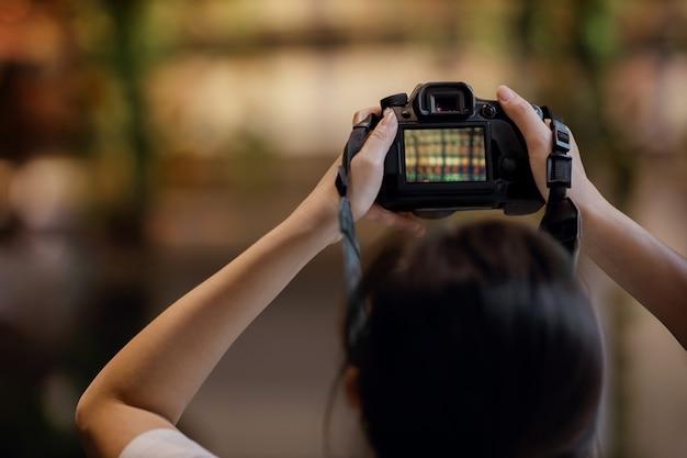 Mujer joven fotógrafo levanta una cámara para tomar fotos.