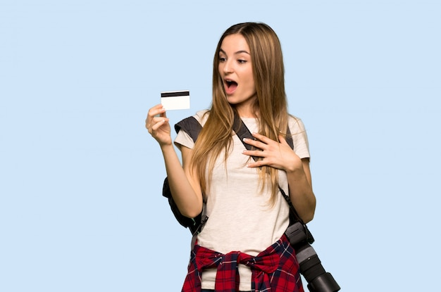 Mujer joven del fotógrafo que sostiene una tarjeta de crédito y sorprendida en fondo azul aislado