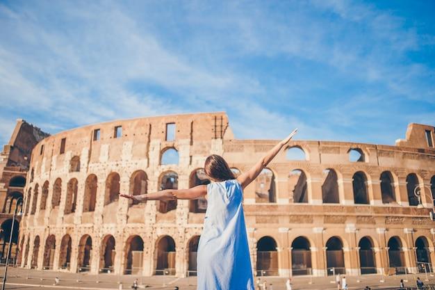 Mujer joven frente al coliseo en vacaciones en roma, italia, chica en europa