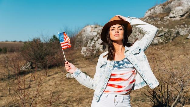 Mujer joven fresca con la bandera de estados unidos posando en la naturaleza