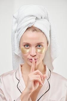 Mujer joven fresca y limpia con una toalla en la cabeza y parches dorados debajo de los ojos manteniendo el dedo índice junto a la boca